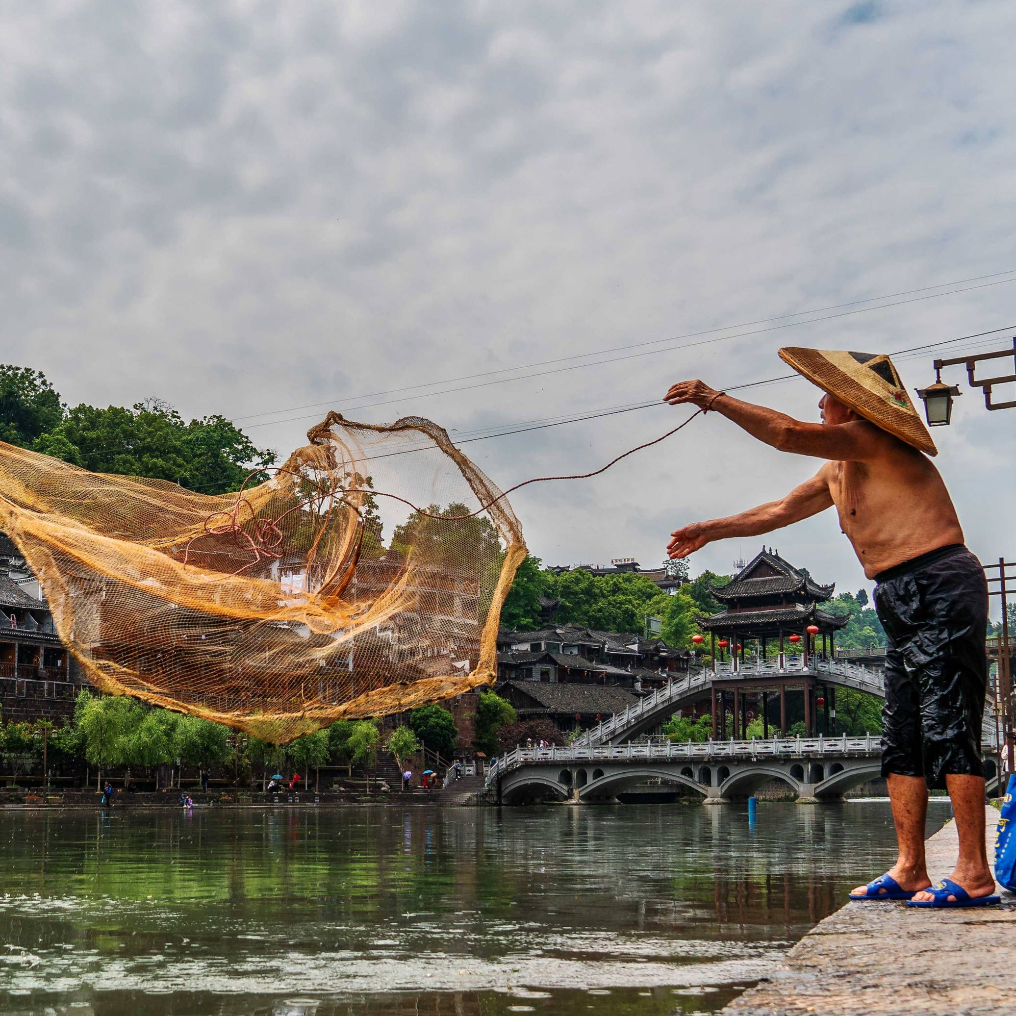 A Fishermen throwing his nets at Tuojiang River