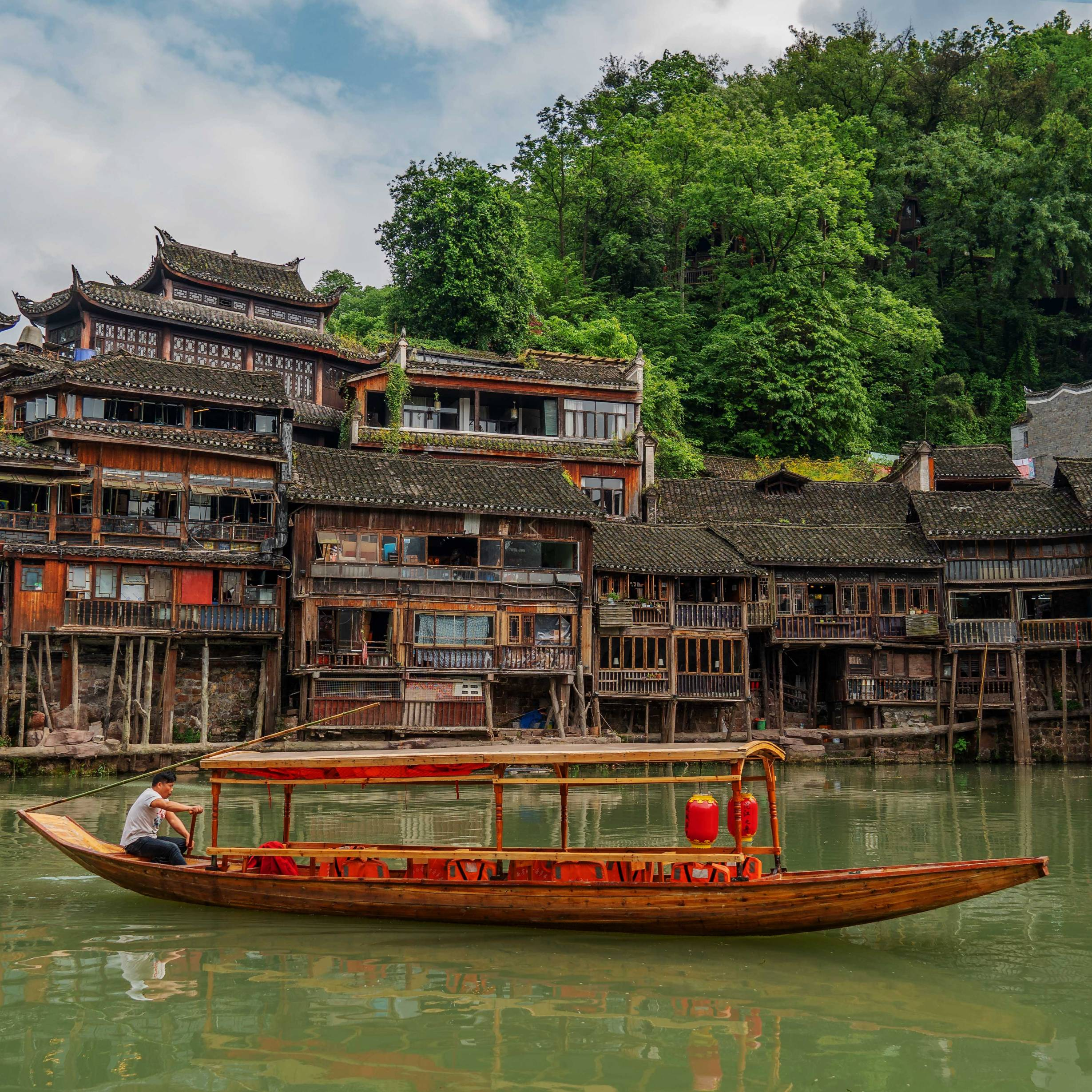 A Traditional Boat in Front of Old Houses in Fenghuang